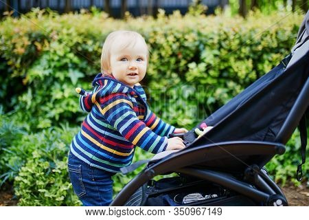 Adorable Happy Toddler Girl Standing Next To Her Pushchair In Park. Smiling Kid Learning How To Walk