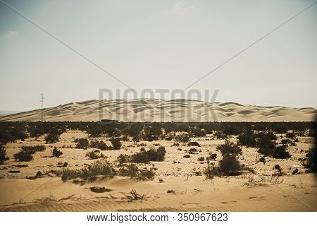 Silhouette Of Power Line By Desert Landscape On A Hazy Day