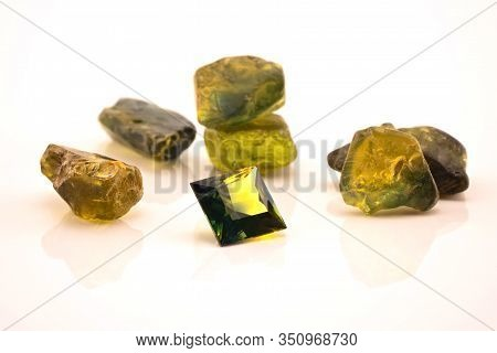 One Square Facet Cut Yellow Green Sapphire Surrounded With Uncut Natural Sapphires, Isolated On A Wh