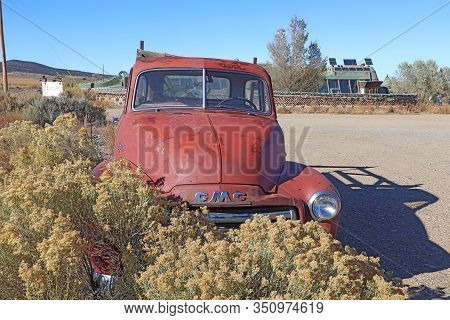 Taos, New Mexico - October 26 2019: Old Car And Earthship Building With Greenhouse And Solar Panels,