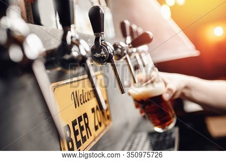 Bartender Pours Beer From Tap Into Glass, Dark Background. Alcohol Craft Drink Concept