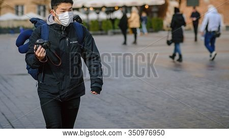 Krakow, Poland- February 02, 2020: Walking Tourist With A Camera In A Protective Mask