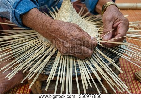 Hands Of Old Artisan Craftsman Elderly Working Weaving Rattan And Bamboo To Make Ancient Handmade Ha