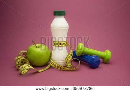Slimming And Weight Loss Concept With Green Apple, Dumbbells And Tape Measure Wound Round A White Pl