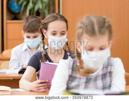 Schoolkids With Medicine Mask On Faces Against Virus Or Flu In Classroom