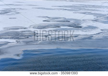 Landscape At The Border Of Blue Water And Frozen, Snowy And Icy Space. Ice Hummocks Near Open Water.