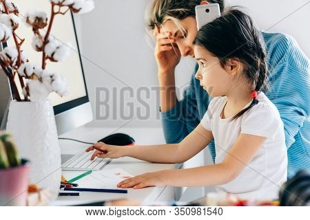 Image Of Busy Young Woman With Daughter Sitting At Home And Working. Young Mother With Toddler Child