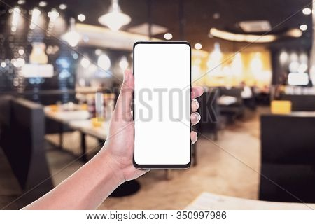 Mockup Image Of Hand Holding White Screen Mobile Phone For Your Advertisement With Blurred Backgroun