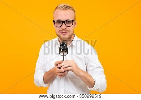 Closeup Portrait Of A Handsome Man In A White Shirt With A Retro Microphone Singing On A Yellow Back