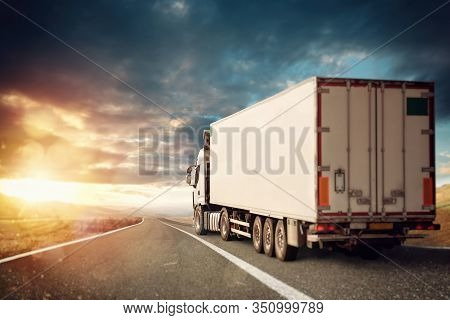White Truck Moving On The Road In A Natural Landscape At Sunset.