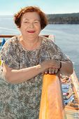 Happy elderly woman stands at board of ship and looks into distance poster