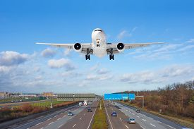 Large Passenger Aircraft Landing Over High Speed Highway