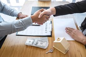 Real Estate Agent Are Shaking Hands After Good Deal And Giving House, Keys To Customer After Signing