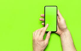 Male Hands Hold A Modern Black Smartphone With Green Blank Screen On Neon Green Background Flat Lay