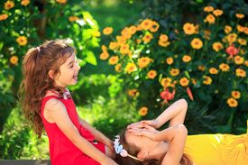Two Cute Little Girls Embracing And Smiling At The  Countryside. Happy Kids Spending Time  Outdoors