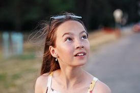 Portrait Of A Beautiful Teenager Girl  Looking Surpriesed Outdoors At Summer Evening