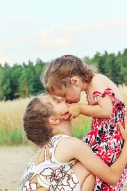 Two Cute Happy Little Girls Is Smiling And Hugging  On Summer Filed