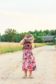 Happy Cute  Little Girl In Retro Outfit Taking Pictures With Old Film Camera.