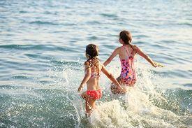 Two Cute Little Girls Playing With Waves By The Sea At Sunset.  Summer Sunny Day, Ocean Coast, Happy