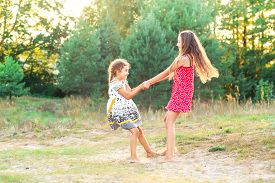 Two Happy Cute  Little Girls Embracing And Dancing At Sunny Summer Day Outdoors