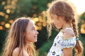 Two Cute Little Girls Looking To Each Other And Smiling At The  Countryside. Happy Kids Spending Tim