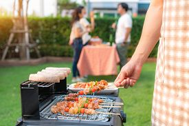 Asian Man Cooking Barbeque Grill And Sausage For A Group Of Friends To Eat Party In Garden At Home.