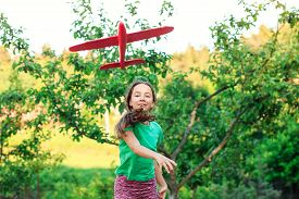 Beautiful Girl Pretend To Be Pilot. Kid Having Fun At Countryside. Summer Vacation And Travel Concep
