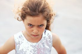 Portrait Of Cute Angry Little Girl. Kid Looking Worried  At Summer Day