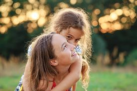 Two Cute Little Girls Hugging And Smiling At The Countryside. Happy Kids Spending Time  Outdoors