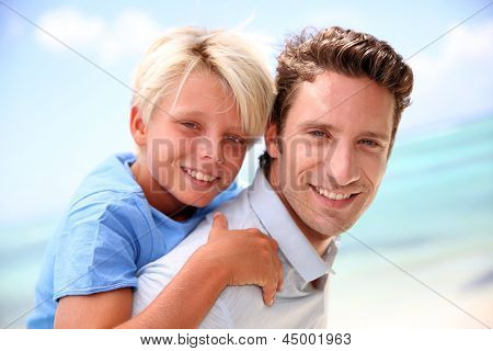 Daddy giving piggyback ride to son by the beach