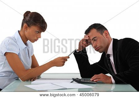 Stern woman with a man using a calculator