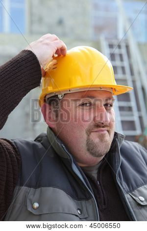 Builder scratching his head