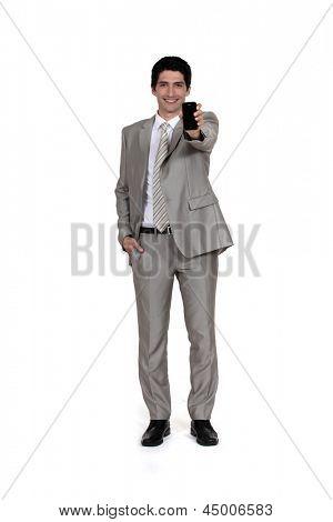 Businessman displaying mobile telephone