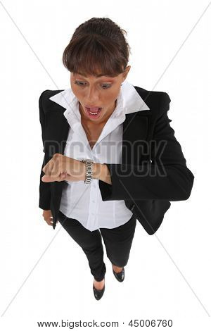 Businesswoman looking at her watch in alarm