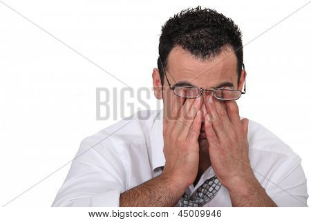 Tired worker rubbing his eyes