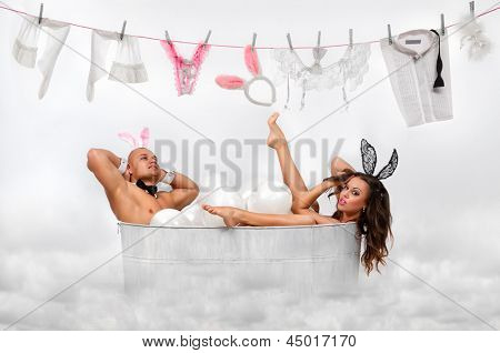 Lovely couple in rabbit costumes sitting in white bath tube in front of several pieces of laundry drying on a clothes line over white
