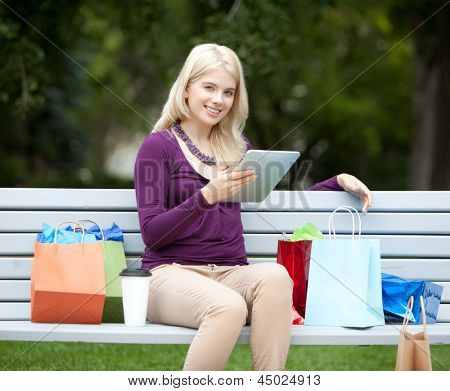 Pretty happy young woman in park with digital tablet and shopping bags