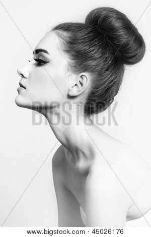 Black and white shot of young beautiful girl with hair bun