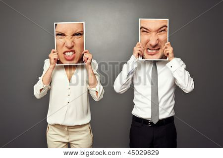 man and woman holding images with big mad faces. concept photo over dark background