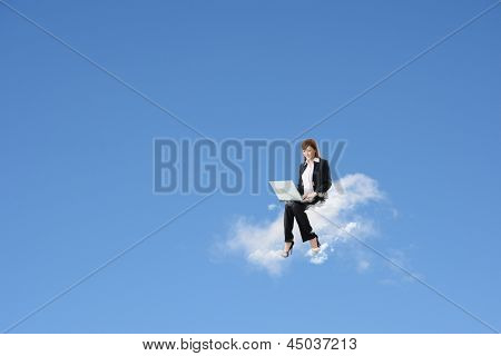 Asian business woman sit on cloud and use laptop over blue sky. Concept of cloud, work, network or new technology in business.