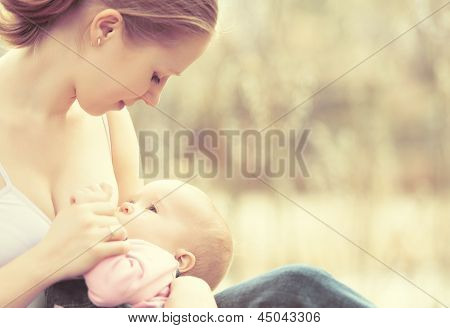 Mother Feeding Her Baby In Nature Outdoors In The Park
