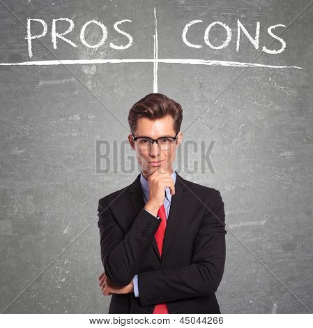 young business man in front of a pros and cons empty list