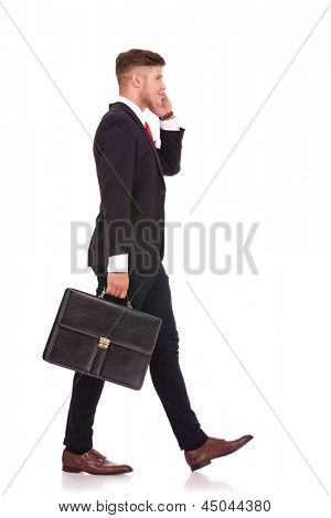 full body picture of a young business man walking to a side with his briefcase and speaking on the phone with a smile on his face. isolated on white background