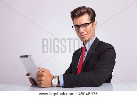 young business man sitting at desk with tablet and looking at the camera with a smile on his face