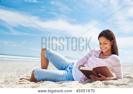 woman reading and relaxing on beach with book