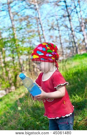 Little Beautiful Girl In Bright Clothes Holding A Bottle In Hand