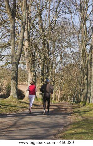 Couple Jogging Through Park