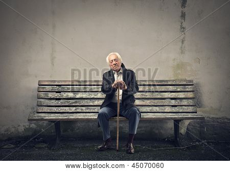 elderly man sleeps sitting on a bench
