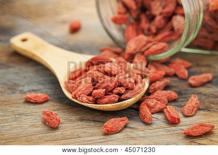 Tibetan goji berries (wolfberry) spilling of the glass jar on a wooden spoon, selective focus