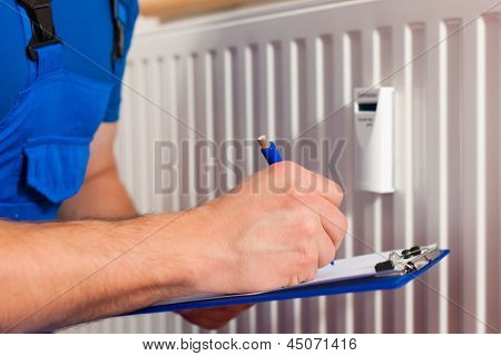 Technician reading the heat meter to check consumption